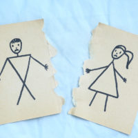 man and woman divorce drawing torn apart on blue background. Divorce couple divorced
